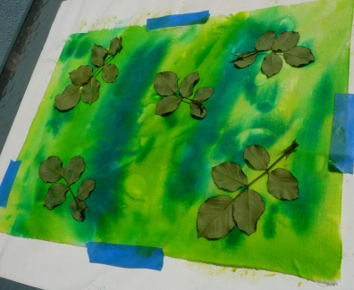 Fresh leaves from a rose bush are arranged on the wet painted surface of the fabric
